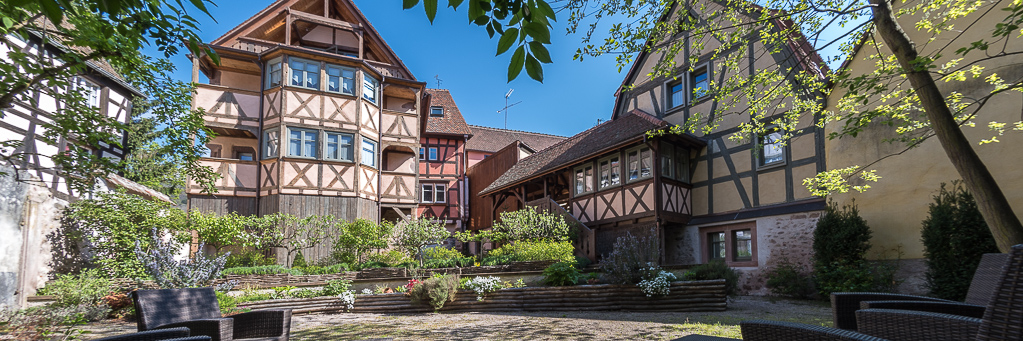 Our Old Winery property: around a garden, 6 outstanding vacation rental apartments newly rebuilt in a former historical winery facing the most famous vineyard in Riquewihr.