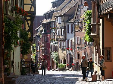Colorful alsatian medieval houses in the main street of Riquewihr, France. The three persons standing on the right side are in front of the famous Hugel winemaker's house.